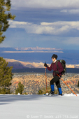 UTAH. USA. Woman snowhoeing on north slope of Boulder Mountain. Dixie National Forest. Sandstone domes of Capitol Reef National Park & San Rafael Swell in distance.