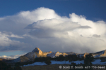 "UTAH. USA. Sandstone ridge called ""The Cocks Comb"" at sunset below cumulus cloud of snow squall. Fremont River Valley. Wayne County."