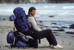 OLYMPIC NATIONAL PARK, WASHINGTON. USA. Young woman backpacker takes a break on the beach near Cape Alava.