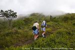 MARTINIQUE. French Antilles. West Indies. Women hikers on trail below cloud-shrouded Mt. Pelée.