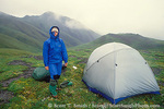 DENALI NATIONAL PARK & PRESERVE, ALASKA. USA. Backpacker at tundra camp. Wet day on Sable Mountain.