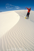 WHITE SANDS NATIONAL MONUMENT, NEW MEXICO. USA. Young woman making big soap bubbles at Heart of the Dunes.