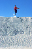 WHITE SANDS NATIONAL MONUMENT, NEW MEXICO. USA. Young woman hiker leaps off dune crest. Heart of the Dunes.