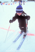 "UTAH. USA. Three-year-old boy competitor crosses finish line in nordic ski ""race"". Bryce Canyon Winter Fest at Ruby's Inn. Near Bryce Canyon National Park."