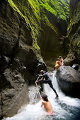 MARTINIQUE. French Antilles. West Indies. Young woman tourist is assisted by native guide as she climbs around falls in narrow slot canyon cut in volcanic rock. Gorge of the Falaise River (Gorges de la Falaise).