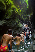 MARTINIQUE. French Antilles. West Indies. Hikers make their way though pools in narrow slot canyon cut in volcanic rock. Gorge of the Falaise River (Gorges de la Falaise).
