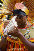 MARTINIQUE. French Antilles. West Indies. Fort-de-France. Costumed band member plays conch shell in parade during Carnival.