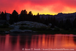 BRIDGER WILDERNESS, WYOMING. USA. Vivid color at dusk is reflected in pool along Pole Creek in Wind River Range. Bridger-Teton National Forest. Color is caused by setting sun shining through smoke from wildfire & virga falling from clouds. Along Continental Divide National Scenic Trail (locally called Fremont Trail).