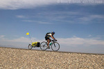 """NEVADA. USA. Female cross-country bicyclist on US Highway 50, """"The Loneliest Road in America.""""  Great Basin."""