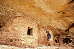 UTAH. USA. Hiker & Anasazi (Ancestral Puebloan) structures. Cedar Mesa. Colorado Plateau. Proposed White Canyon BLM Wilderness.