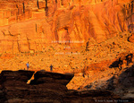 CANYONLANDS NATIONAL PARK, UTAH. USA. Young rock scramblers below cliffs at sunset. Along Green River.