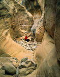 UTAH. USA. Hiker takes a break in narrows of Little Wildhorse Canyon. San Rafael Swell. Proposed San Rafael Swell BLM Wilderness.