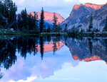 SAWTOOTH WILDERNESS, IDAHO. USA. Cumulus clouds & Mount Everly reflected in unnamed lake at sunset. Sawtooth Mountains. Sawtooth National Forest. Sawtooth National Recreation Area. Rocky Mountains.