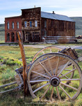 Bodie State Park, California. USA. Wagon & buildings in ghost town of Bodie. Dechambeau Hotel/Post Office (left), Odd Fellows Lodge (right).