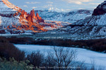 Utah. USA. Frozen-over Colorado River below Fisher Towers and La Sal Mountains in winter.
