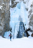 Yellowstone National Park, Wyoming, USA. Woman cross-country skier and ice-cloaked Fairy Falls in winter.