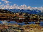 DENALI STATE PARK, ALASKA. USA. Tarn & tundra in autumn. Kesugi Ridge. Moon above Denali (Mt. McKinley) in distance.
