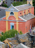 Corsica. France. Europe. Colorful church of St. Julie rises above slate roofs of houses in village of Nonza. Cap Corse.