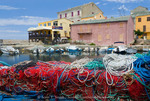 Corsica. France. Europe. Fishing nets stacked on dock at village of Centuri. Cap Corse.