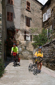 Corsica. France. Europe. Bicyclists walk bikes down very steep road in village of Oletta.