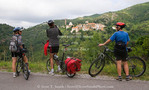 Corsica. France. Europe. Bicyclists below mountain village of Piéve.