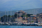 Corsica. France. Europe. Mast of boats & breakwater below citadel & other buildings of St. Florent.