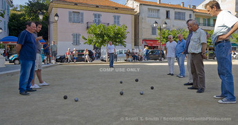 Corsica. France. Europe. Local men playing pétanque in public square on summer evening in St. Florent.