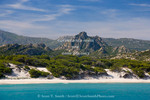 Corsica. France. Europe. White sand & clear water at Saleccio Beach below rugged terrain of Désert des Agriates.
