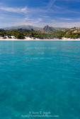 Corsica. France. Europe. Clear water & white sand at Saleccio Beach below rugged terrain of Désert des Agriates.