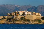 Corsica. France. Europe.. Buildings of the old city at Calvi within the walls of the historic Venetian fortress. Monte Padru & other peaks in distance.