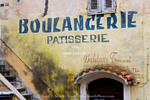 Corsica. France. Europe. Old sign painted on wall in old city section of Corte.