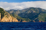 Corsica. France. Europe. Rugged coast near Galeria. Genoese tower visible in distance at mouth of canyon.
