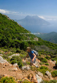 Corsica. France. Europe. Woman hiker on the Mare e Monte Nord Trail (Sea and Mountains North Trail) on the Scandola Penisula. Villgae of Girolata, Gulf of Porto, &  Monte Ravu in distance. Corsican Regional Park (Parc Naturel Regional de Corse). Girolata is accessible only by boat or foot.
