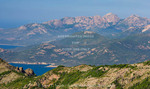 Corsica. France. Europe. View of Monte Cintu from summit along the Mare e Monte Nord Trail (Sea and Mountains North Trail) on the Scandola Penisula. Corsican Regional Park (Parc Naturel Regional de Corse). Golfe del Galeria is visible. Wind turbines on distant ridge.