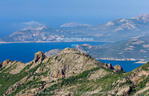 Corsica. France. Europe.View from summit along the Mare e Monte Nord Trail (Sea and Mountains North Trail) on the Scandola Penisula. Corsican Regional Park (Parc Naturel Regional de Corse). Golfe del Galeria is visible. Wind turbines on distant ridge.