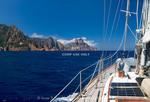 Corsica. France. Europe. Sailboat approaching Cape Rossu (Capu Rossu) in Golfe de Porto. Mediterranean Sea.
