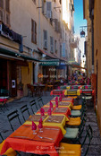Corsica. France. Europe. Tables of cafe set up in narrow street in preparation for the evening's diners. Ajaccio.