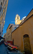 Corsica. France. Europe. Church steeple rises above narrow street with tables set up outside cafe in Ajaccio.