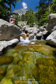 Corsica. France. Europe. Hiker takes a break on granite boulder at pool of clear water near Cascades des Anglais. Along the GR20 trail (aka, Fra li Monte). Monte d'Oro in distance.