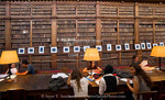 Corsica. France. Europe. Students study below shelves of old books in Ajaccio municipal library.