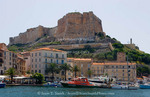 Corsica. France. Europe. Walled citadel enclosing the old city rises above the inner harbor at Bonifacio.