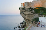 Corsica. France. Europe. Buildings of the old city of Bonifacio built on overhanging limestone cliff. Outside the walls of the citadel at dusk.