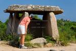 Corsica. France. Europe. Visitor investigates Fontanaccia Dolmen (Dolmen de Fontanaccia). Bronze-age granite megalith. Cauria Archeological Site (Site archéologique Cauria).