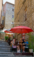 Corsica. France. Europe. Cafe tables in narrow alley in village of Sartene.