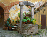 Stone well and stairs with potted flowers in a courtyard of the hill town of San Querico d'Orcia