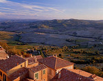 Colorful buildings and tiled roofs of Montepulciano with the rolling hills of the countryside in the background