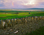 Rainbow and clearing storm clouds over stone fences and green hillsides near the village of Lahinch on Liscannor Bay in County Clare, Ireland