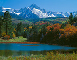 Mount Sneffels rises above forested foothills in fall color and a small mountain lake in Uncompahgre National Forest, CO