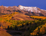 Evening light on aspen covered foothills and snow dusted peaks of the San Juan range in Uncompahgre National Forest, CO