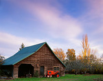 B&S weathered barn and orange tractor under evening clouds on Vashon Island, WA